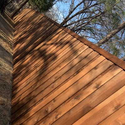 Cedar fence with fence stain on it. The sun is setting in this fenced in backyard.