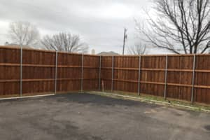 The backside of a fence with an automated gate on it. This is an 8 foot wood fence